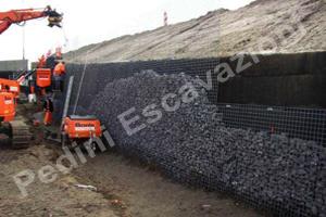 Sistema Muralex®. Muro in terra rinforzata subverticale con paramento in pietrame e rete elettrosaldata zincata di contenimento.